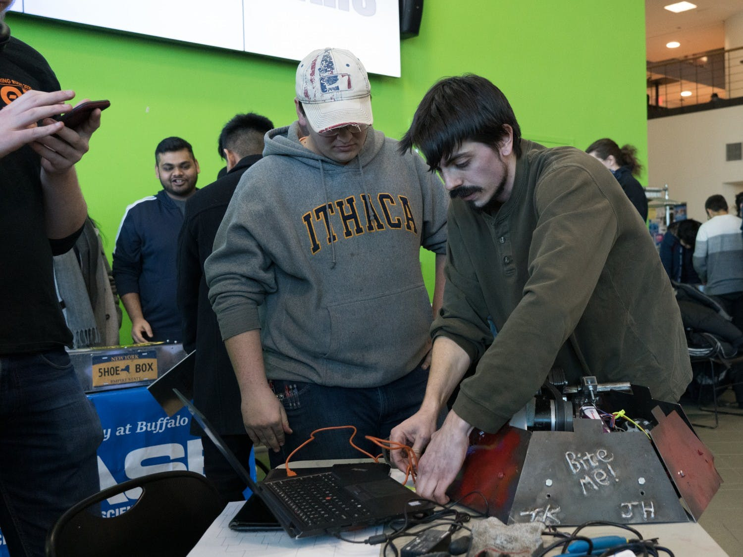 Industrial and systems engineering major Josh Hulburt (left)and mechanical engineering major Troy Kilian make repairs to their robot after winning in the arena during the previous round.