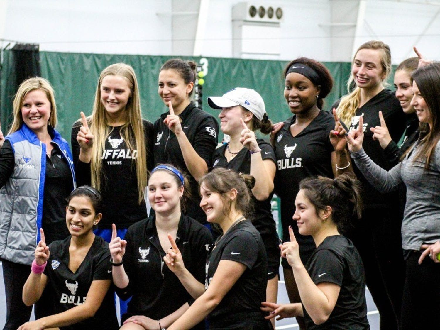 The Bulls pose to celebrate their win. The women's tennis team opened its 2019 spring season with two dominating performances.