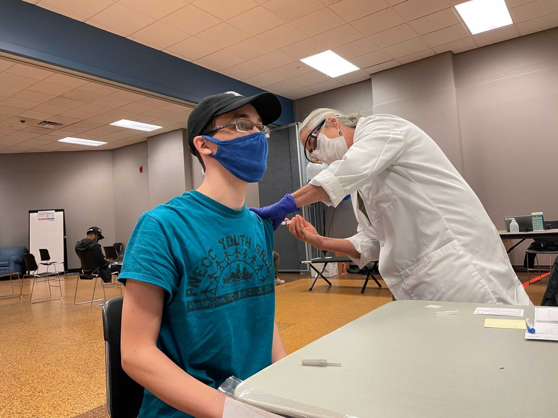 Josh Atkinson, a senior geology major, receives the Johnson & Johnson vaccine at UB's North Campus vaccination site.