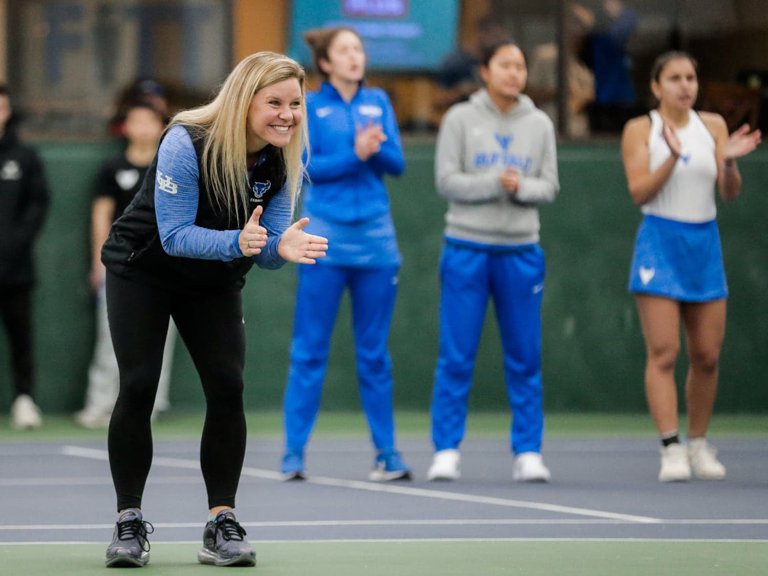 Women's tennis coach Kristen Maines coaching her team.