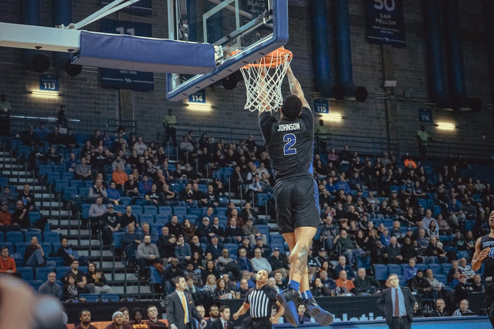 <p>Senior guard Antwain Johnson goes in for the dunk.</p>