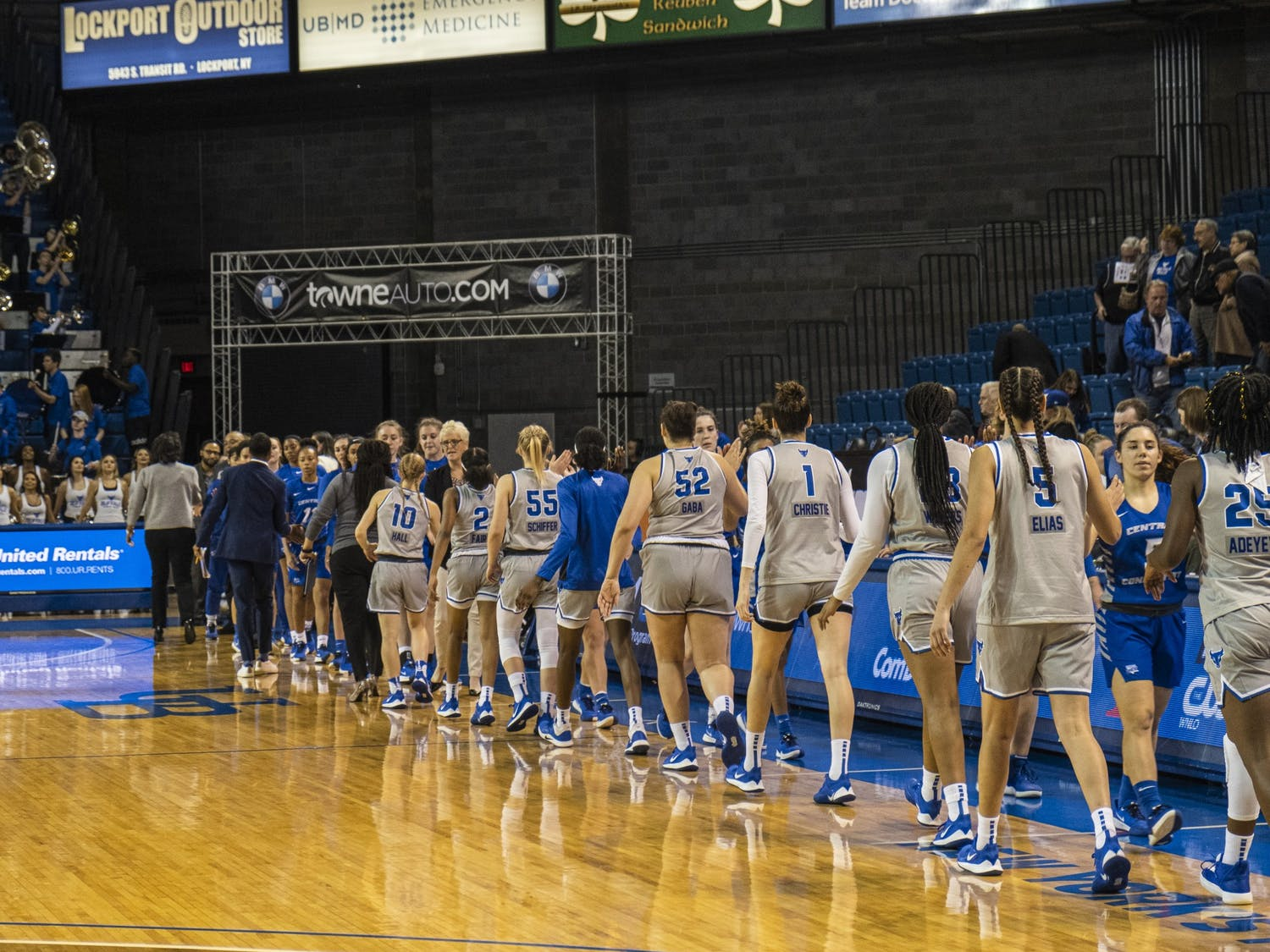 The women's basketball team congratulates an opponent at the end of a game.