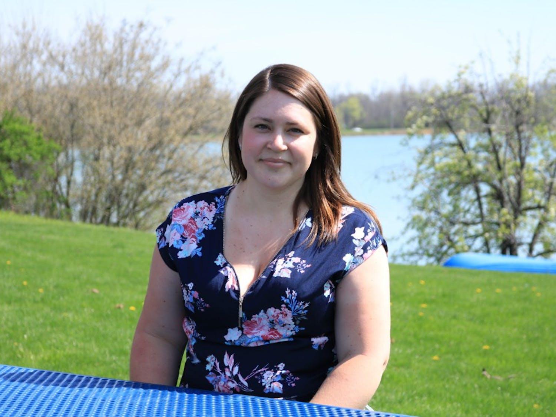 Lauren Mojeski, a senior history major, sits in front of Lake LaSalle.