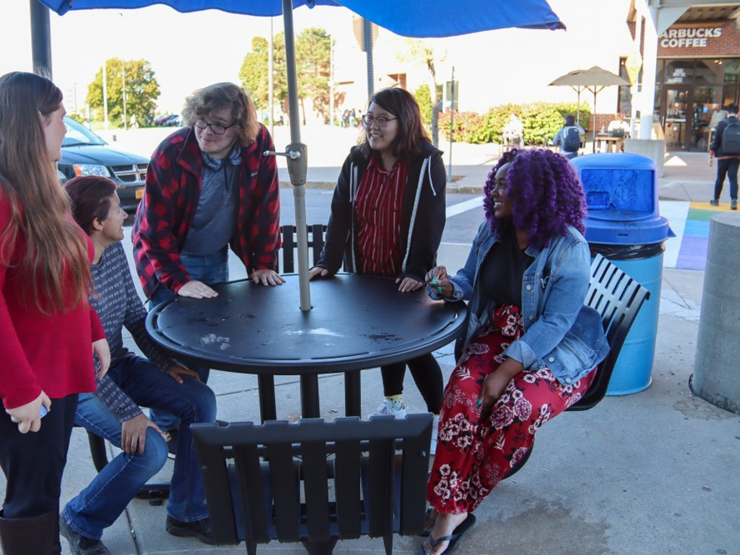 The cosplay club eboard discusses upcoming meetings in front of the Student Union.