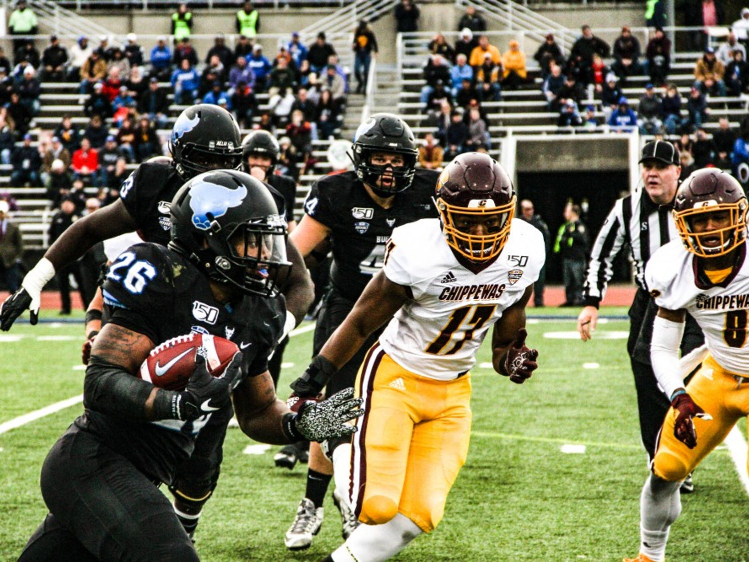 The Buffalo Bulls' running back Jaret Patterson rushes with the ball as the Central Michigan Chippewas close in.