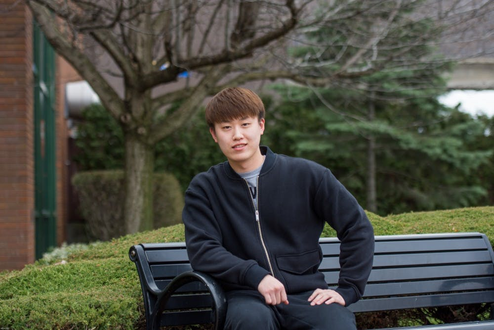 <p>Mingi Jin, a junior chemical engineering major, sits outside of the Student Union. Jin has been in the U.S. for four years and says he has made no American friends and has never been to a football or basketball game at UB.&nbsp;</p>