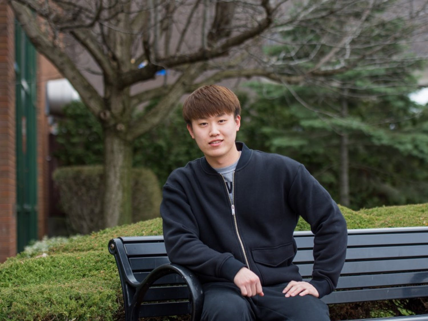 Mingi Jin, a junior chemical engineering major, sits outside of the Student Union. Jin has been in the U.S. for four years and says he has made no American friends and has never been to a football or basketball game at UB.