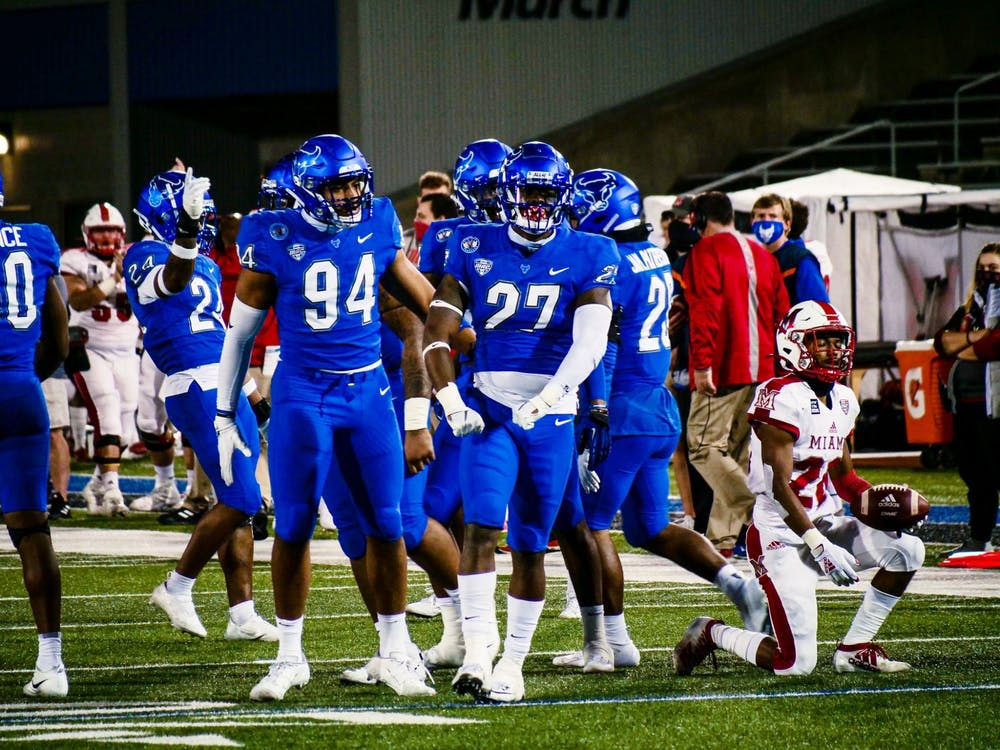 <p>Junior defensive end Eric Black (94) and graduate linebacker Tyree Thompson (27) celebrate after making a defensive stop.</p>