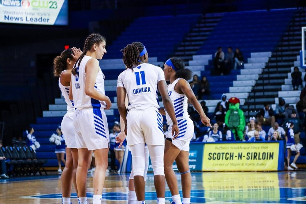 <p>UB women's basketball players huddle up near mid-court during a game last season.</p>