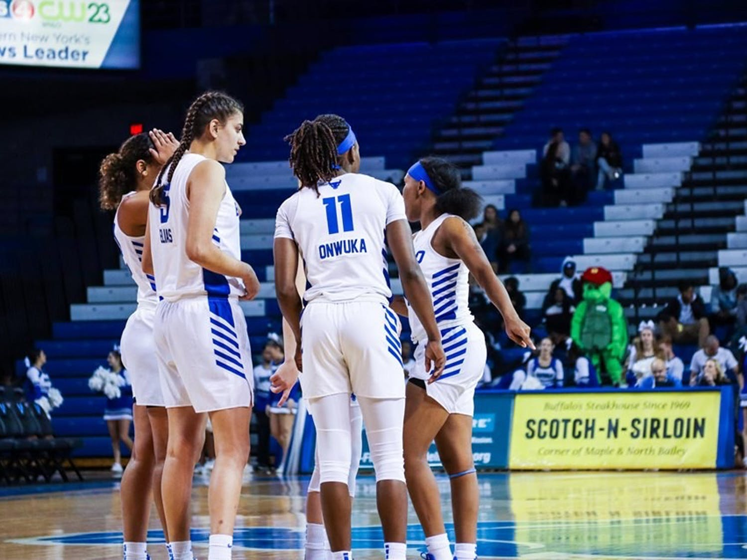 UB women's basketball players huddle up near mid-court during a game last season.