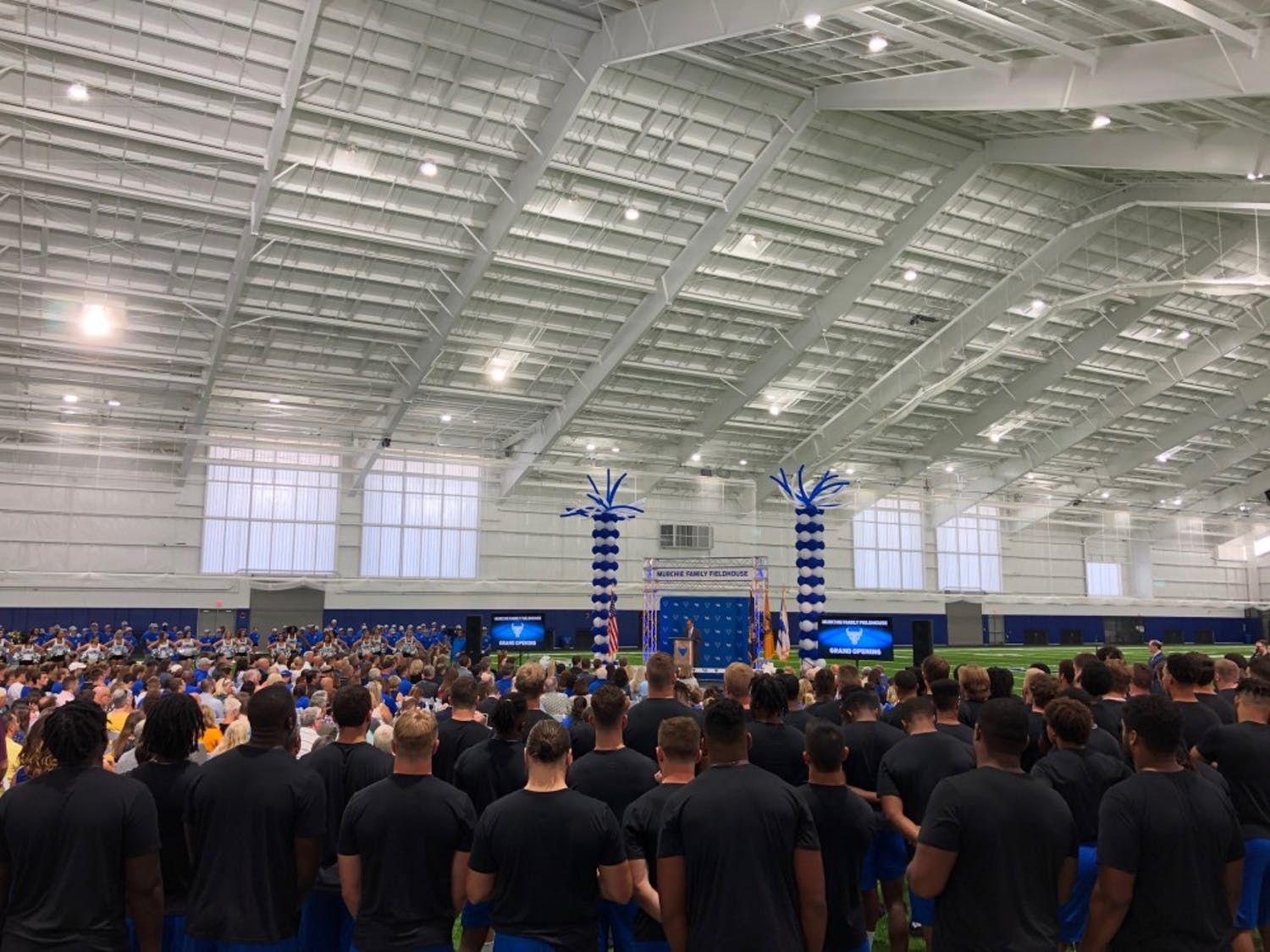 The UB football team watches on during a speech at the Murchie Family Fieldhouse grand opening Tuesday.
