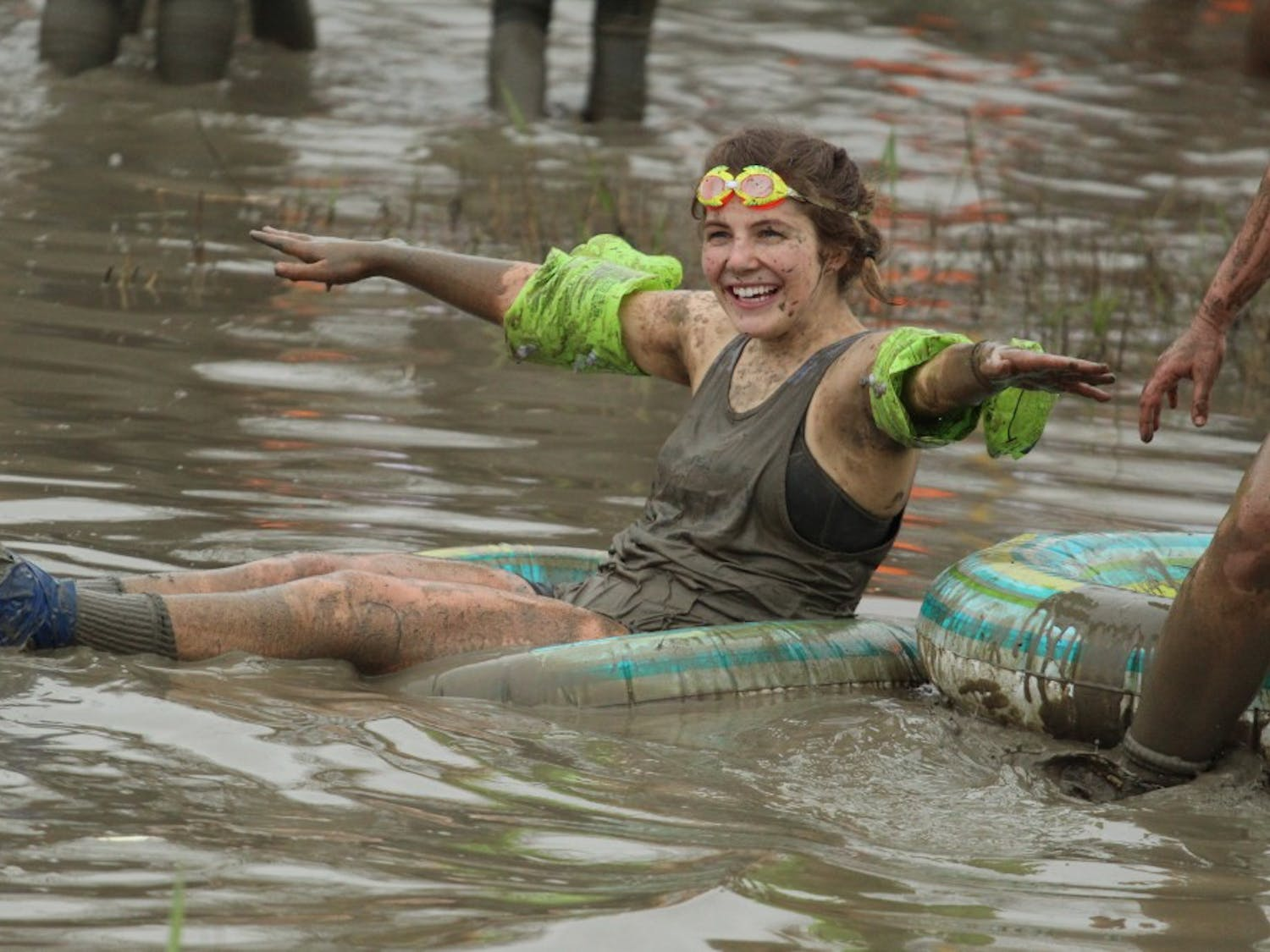 """UB student uses an inflatable tube in the """"mud pool."""" Eliminated team members found ways to continue to enjoy the pit after their matches."""