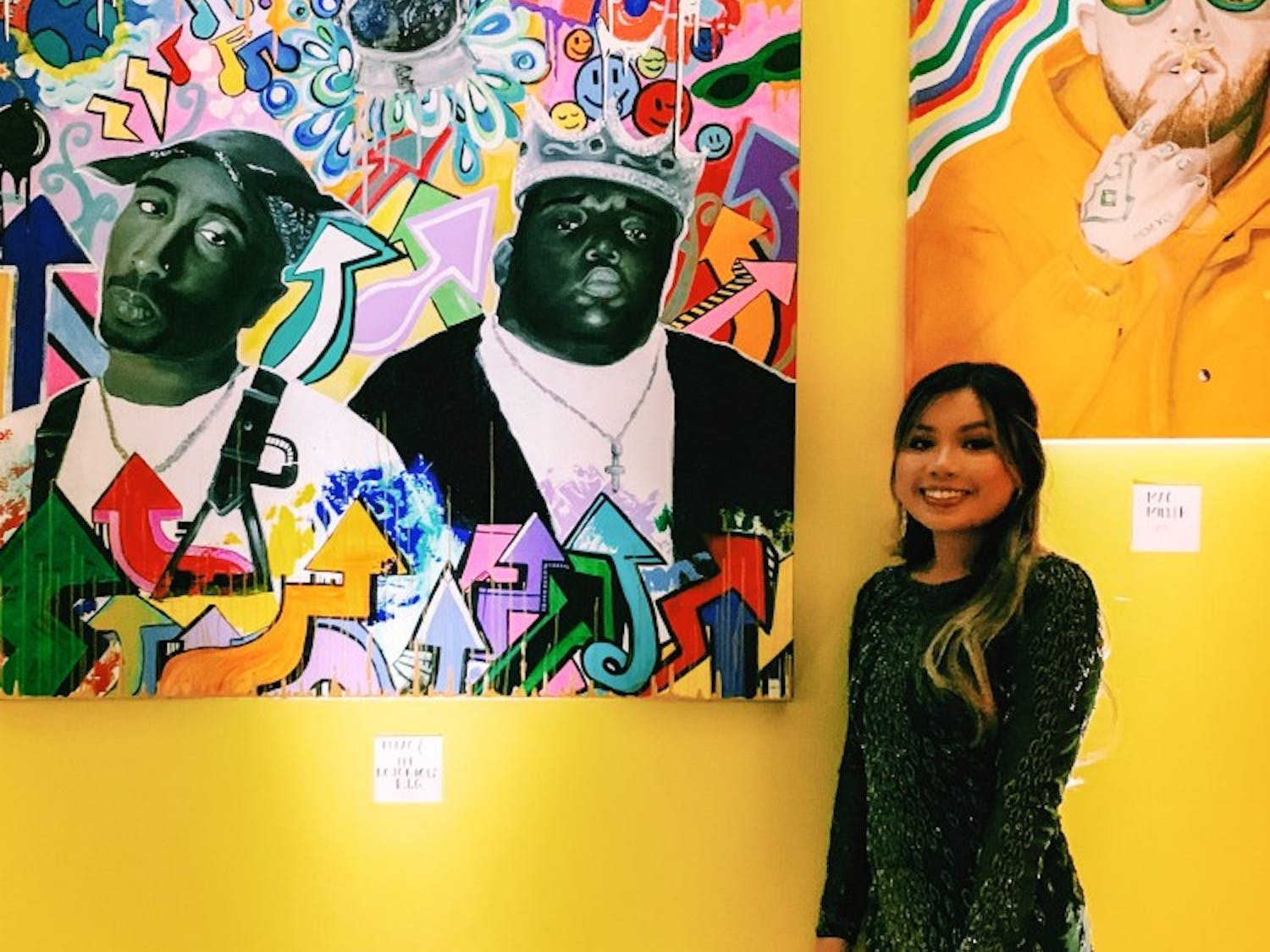 Jasmine To poses with her paintings.