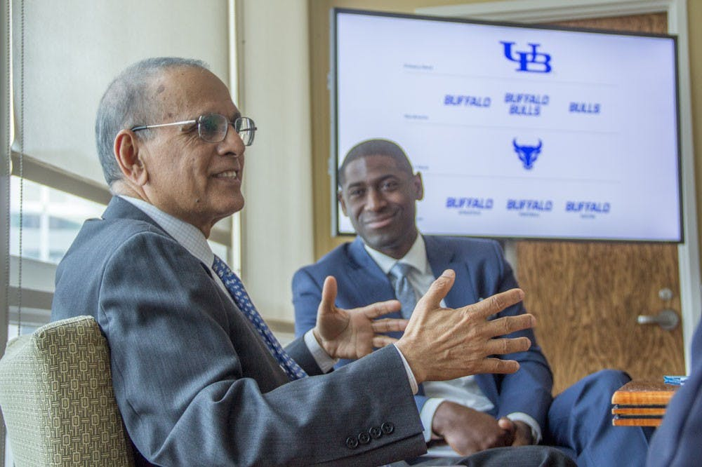 """<p>Satish Tripathi (front), UB president and Allen Greene, UB Athletic Director (back) discuss UB's recently launched branding initiative, which looks to unite all of UB's schools and units around the """"University at Buffalo"""" name.</p>"""