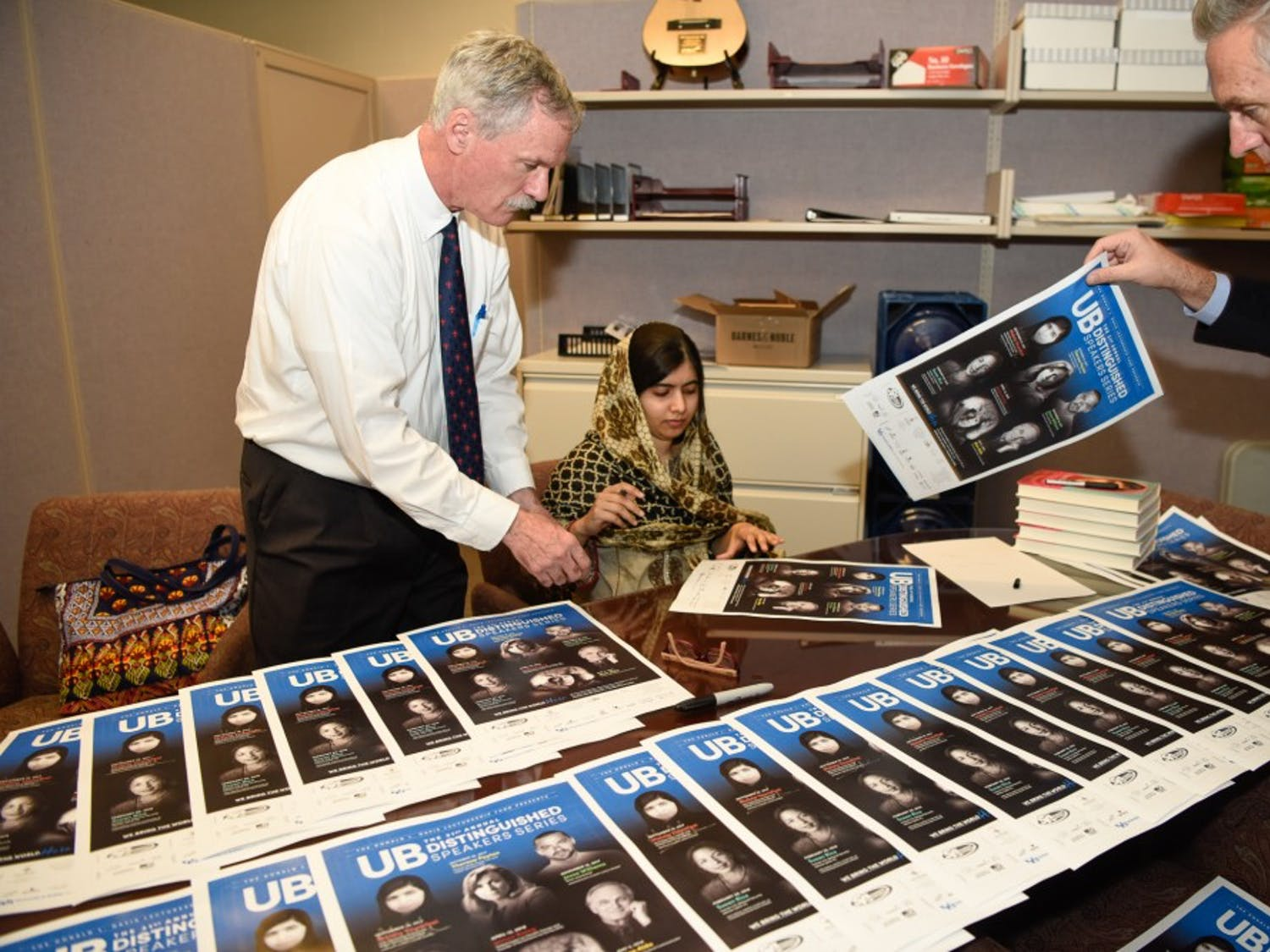 William Regan (left) hands Distinguished Speakers Series posters to Nobel Peace Prize winner and activist Malala Yousafzai. Regan's office, the office of University Events, has hosted the lecture-based, educative series for over three decades at UB.