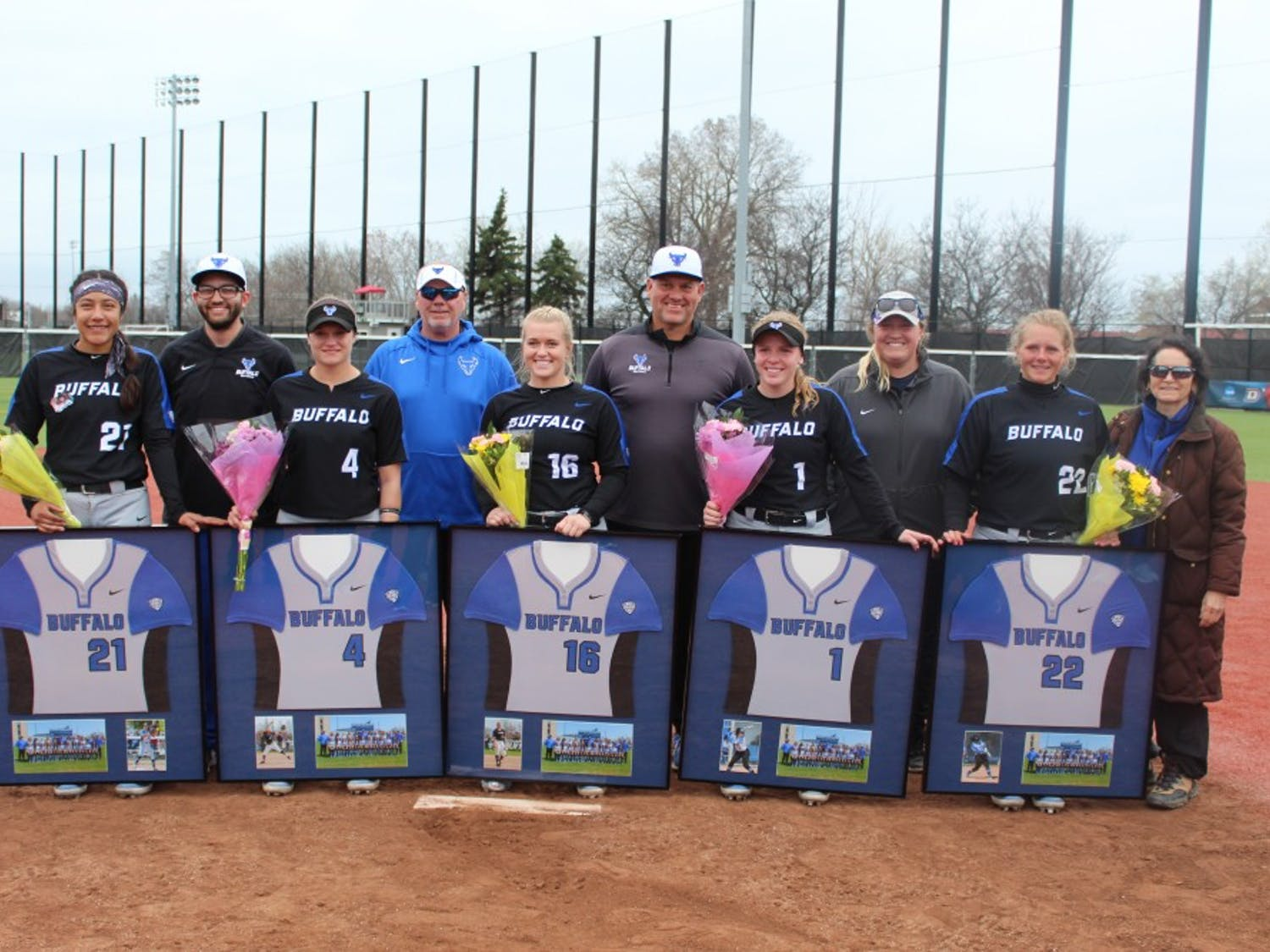 Alysaa Cuevas, Lace Smith, Ally Power, Alissa Karjel and Catrell Robertson stand with members of the UB softball coaching staff and administrators following the end of their doubleheader on Saturday.
