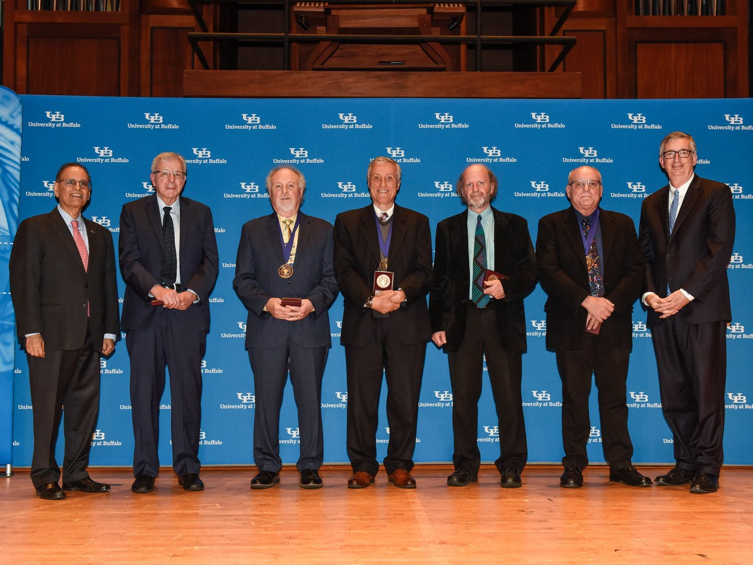 Interim Provost A. Scott Weber (far right) and President Satish Tripathi (far left) stand with 2019 SUNY Distinguished Professors.