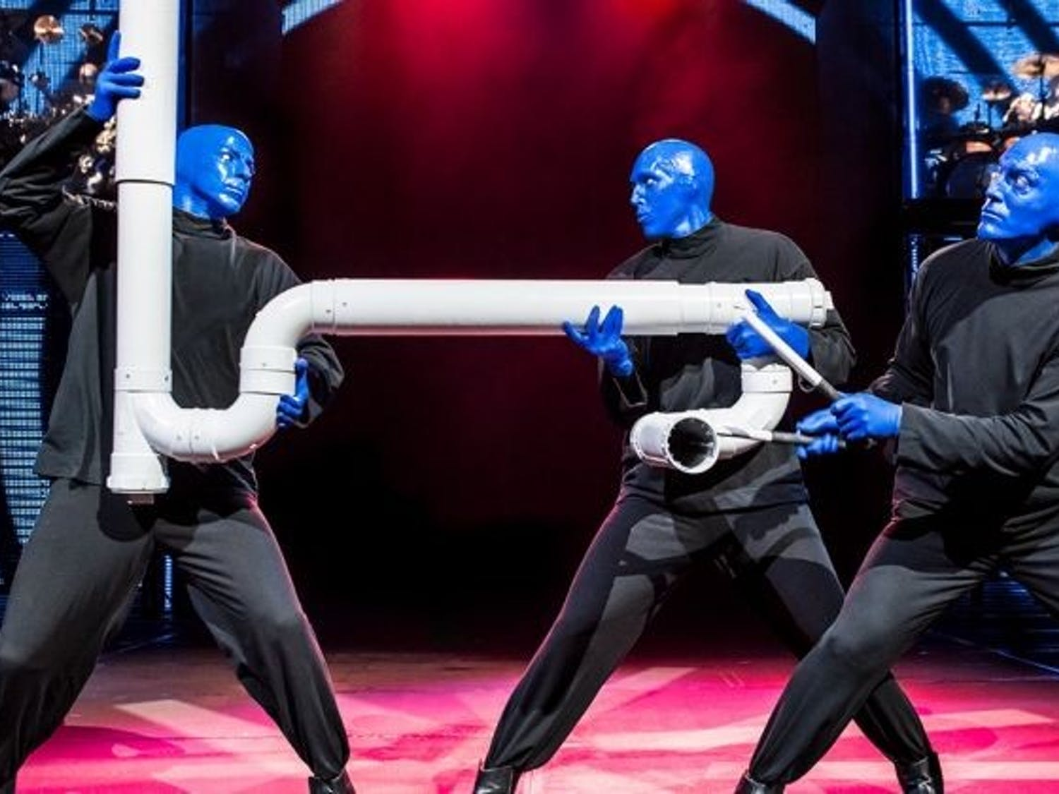 The three blue men playing with one of their signature instruments, the drumbone.