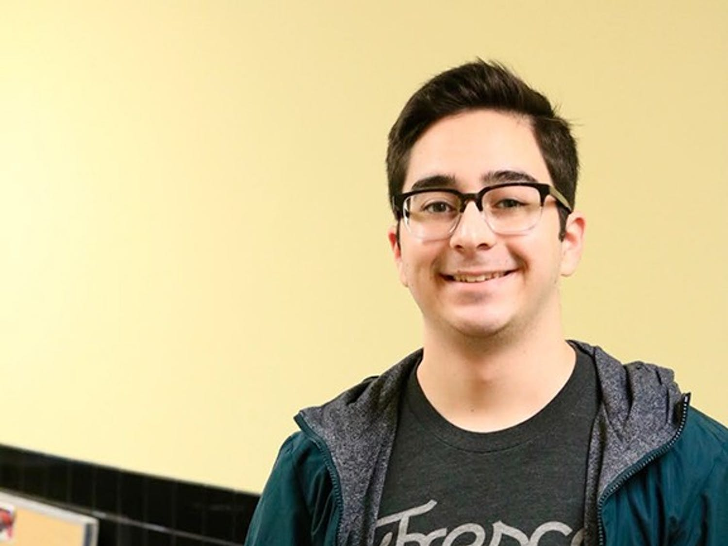 Arthur De Araujo, sophomore computer science major, poses next to the icon for his Lecture Buddy app. The app translates a lecture into text and highlights important keywords.