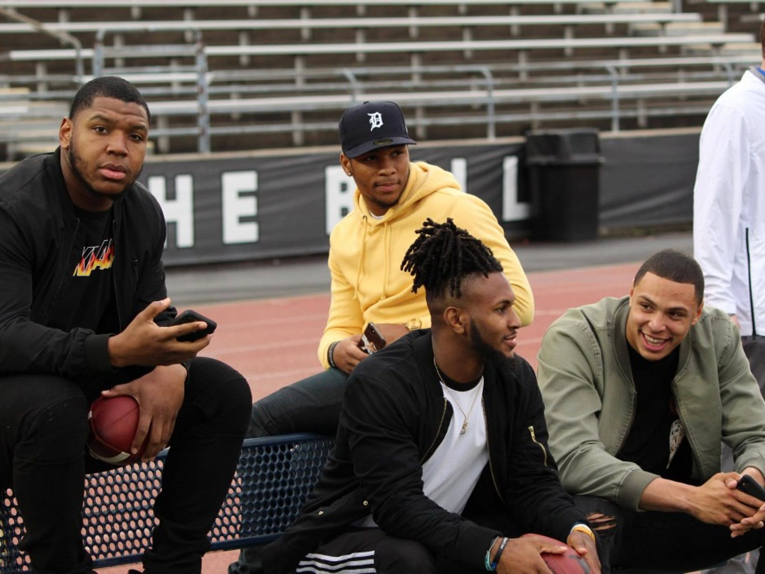 UB football alum Chuck Harris, Cameron Lewis, Anthony Johnson and Tyree Jackson sit on the sidelines during the annual spring football game. All four signed with an NFL team this weekend.