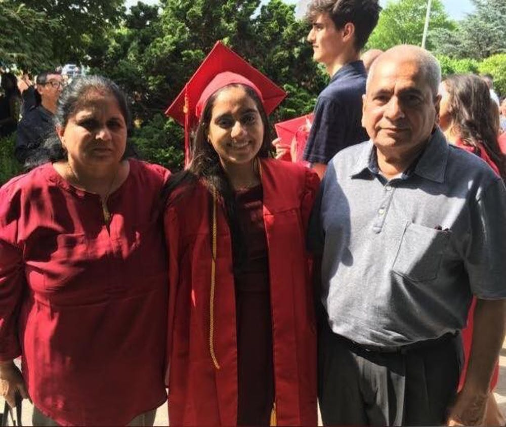<p>Minnoli Aya (center) with her mother Madhvi and her father at her high school graduation.</p>