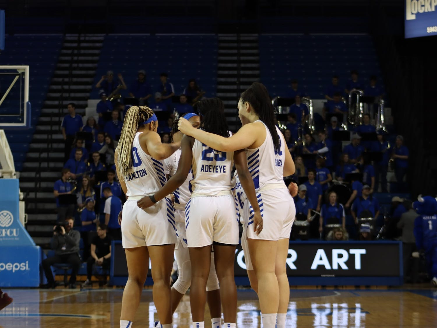 The women's basketball team gather in a team huddle before the start of a game.