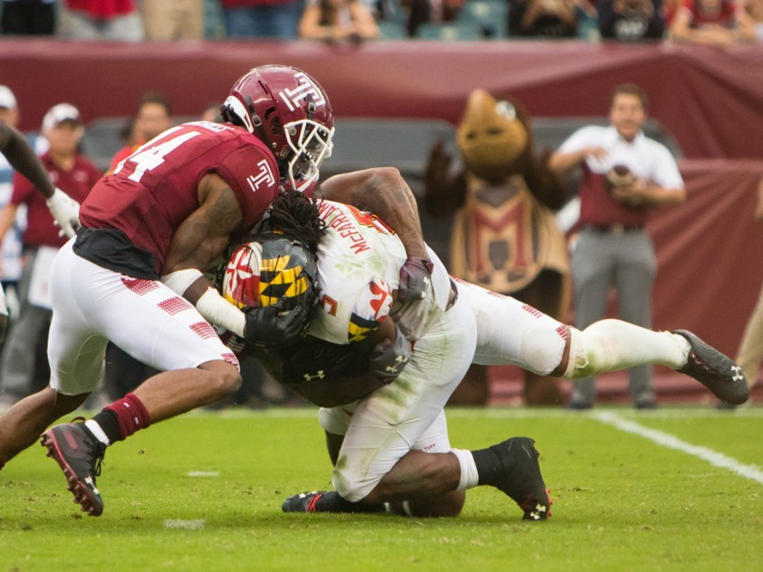 Redshirt-sophomore cornerback Christian Braswell (left) assists senior linebacker Shaun Bradley in a tackle during the fourth quarter in the Owls' game against Maryland at Lincoln Financial Field on Sept. 14, 2019.