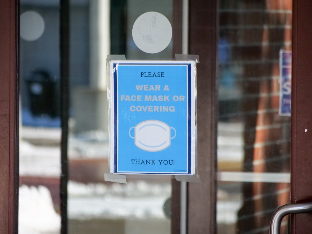 A sign on the door to the Student Union asks visitors to wear a mask when walking around campus.