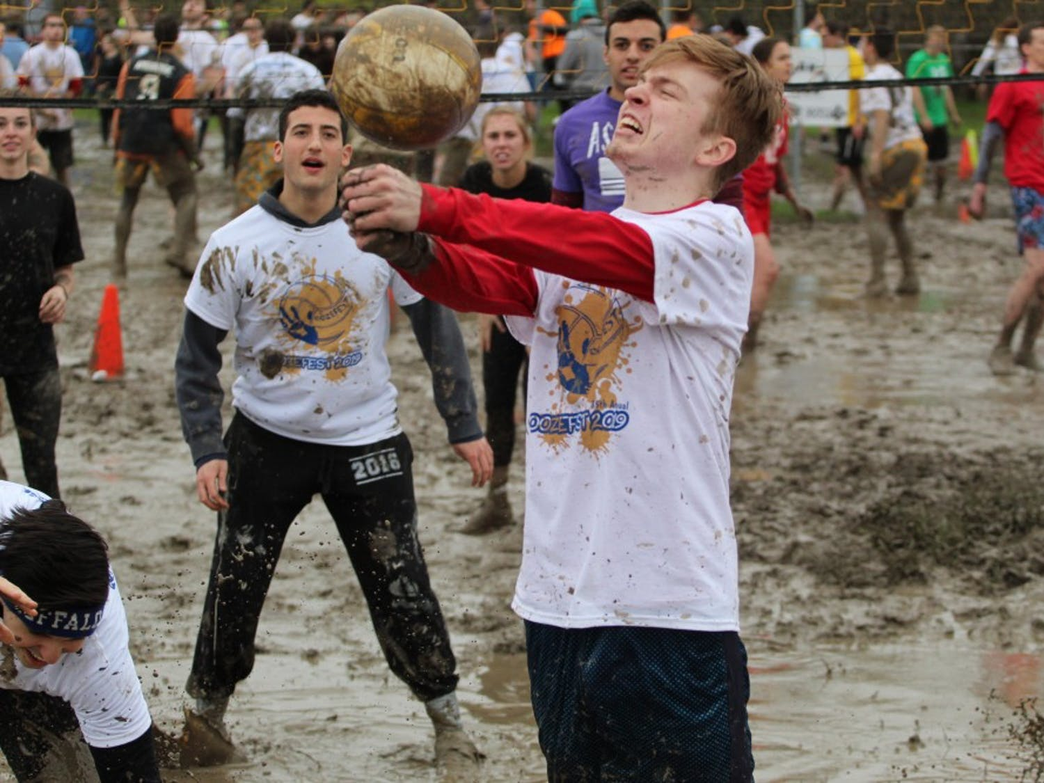 """UB student receives """"back-splash"""" from a muddy volleyball. Many students left Oozefest with muddy faces from similar experiences."""