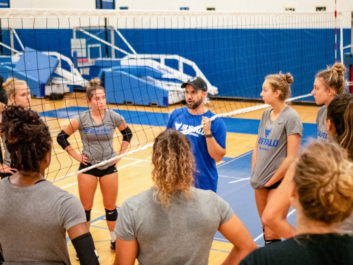 Coach Smith instructing the volleyball team during a practice at Alumni Arena.