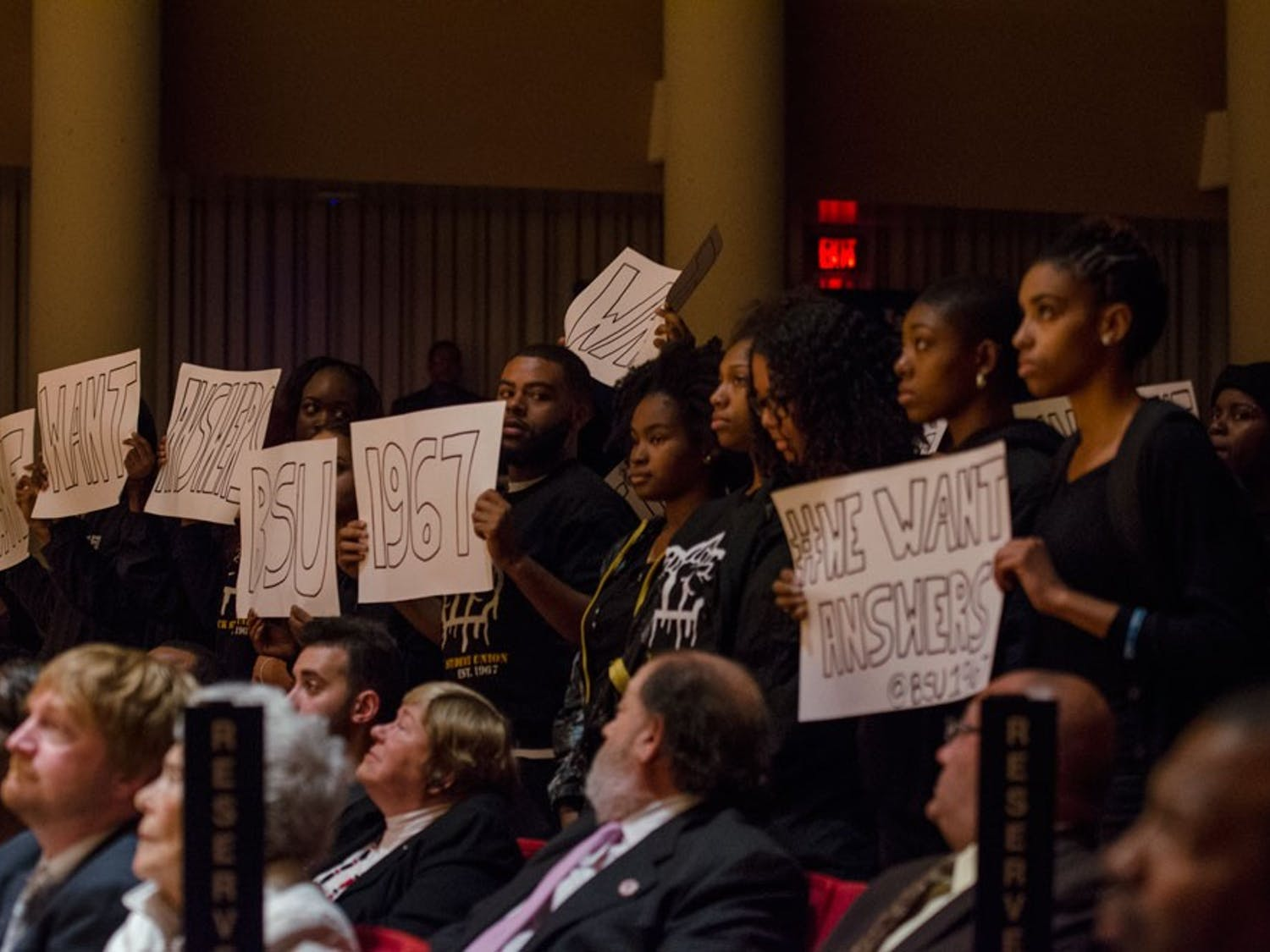 """Members of the Black Student Union held a peaceful protest during President Satish Tripathi's annual State of theUniversityAddressin response to the controversial race art project and the university's response. Students stood and raised white posters in the air that read """"We Want Answers"""" and left early to stand in the Slee Hall lobby and protest as people grabbed refreshments."""