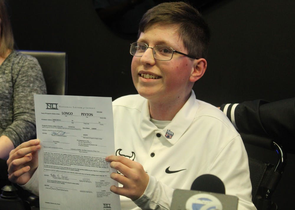 <p>Sixteen-year old Peyton Longo holds up his National Letter of Intent after signing on as a member of the Bulls. Longo suffers from a form of muscular dystrophy and has joined the team through Team IMPACT.</p>