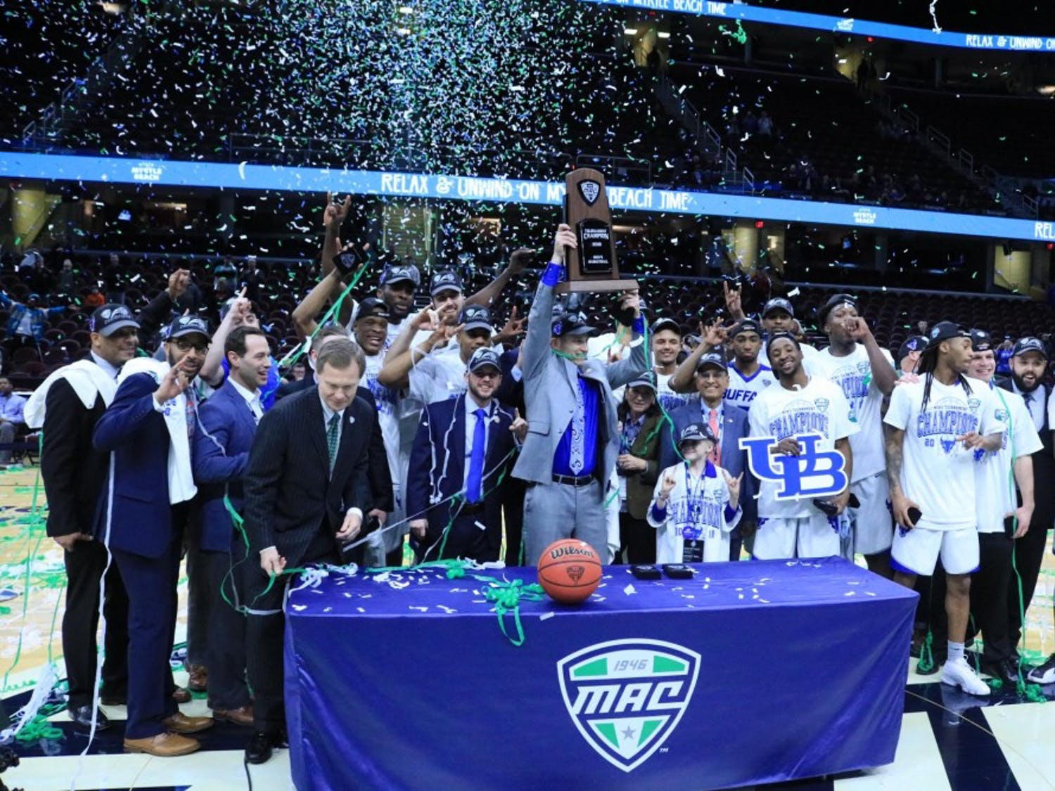 Bulls head coach Nate Oats lifts the MAC tournament trophy over his head. The Bulls have won three of the last four MAC tournaments and are both the MAC regular season and MAC tournament champions this year.