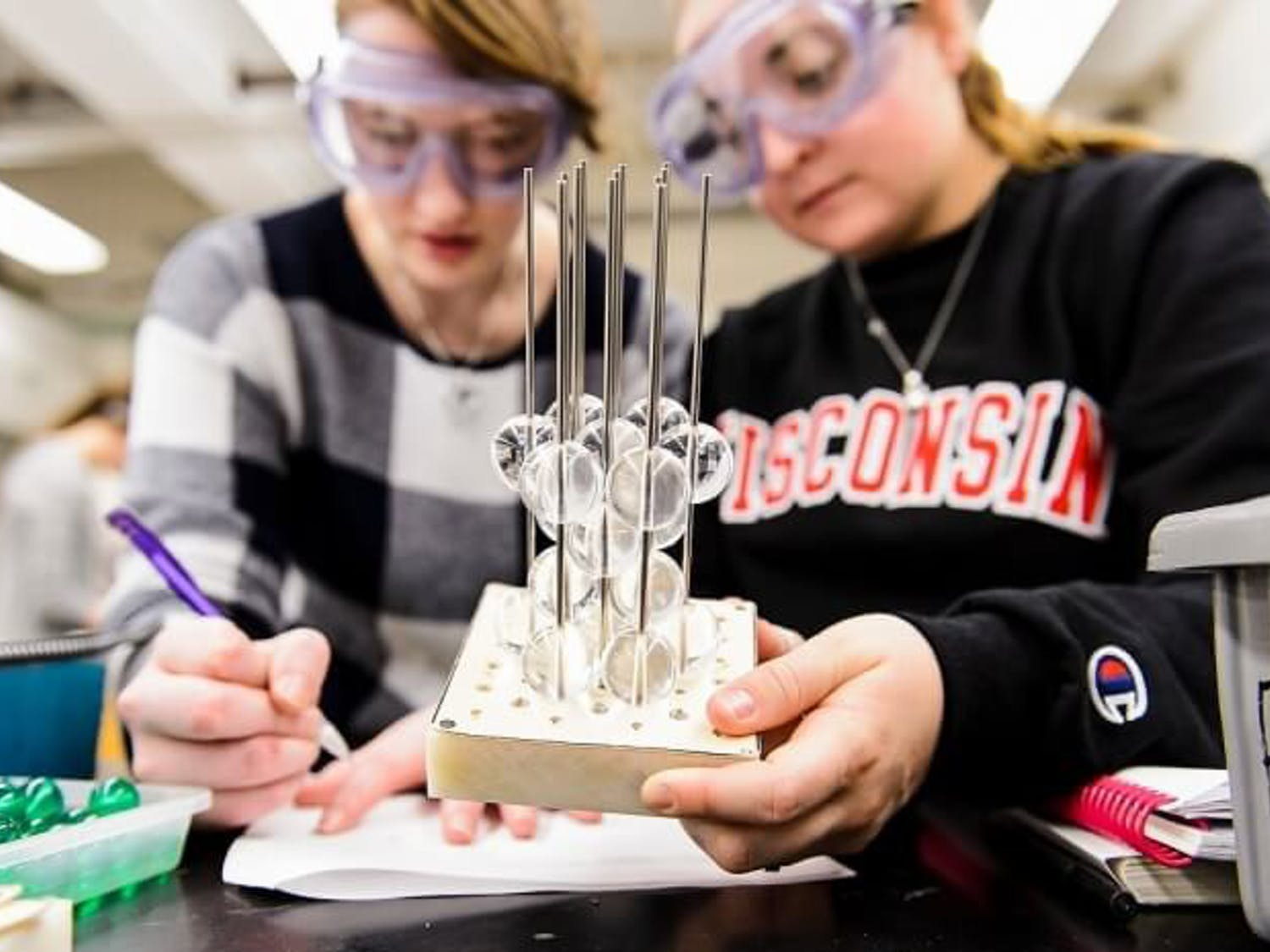Two UW-Madison students participate in a science experiment in their chemistry class.