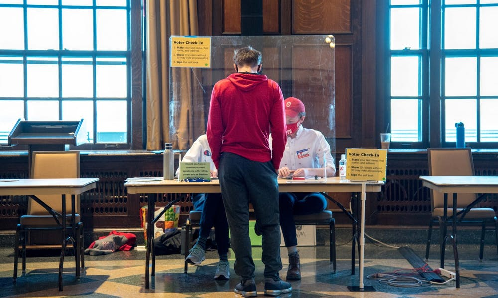 Photo of student getting a ballot to vote.