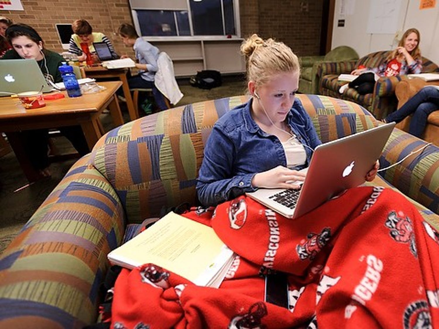 Home is where the Wisconsin Badger football blanket is. First-year undergraduate Erin Wendt settles in with her laptop computer to study in the Women In Science and Engineering (WISE) den in Sellery Residence Hall at the University of Wisconsin-Madison during the evening of April 17, 2013. In the background are fellow WISE residents Bailee Stark, left, and Maria Bakker. The photograph was created for #UWRightNow, a 24-hour multimedia and social-network project. (Photo by Jeff Miller/UW-Madison)