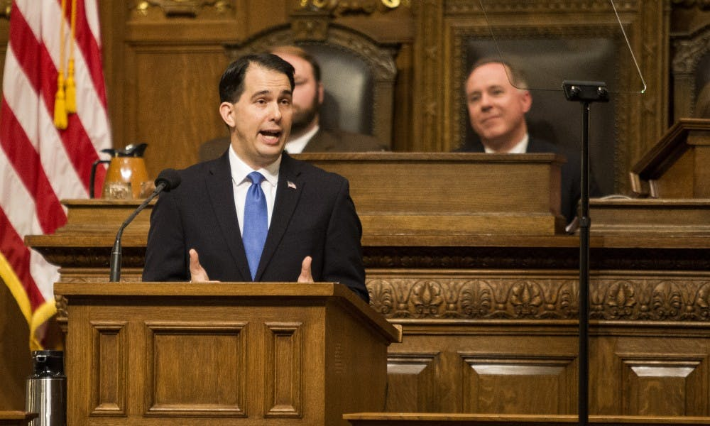Gov. Scott Walker signed over 20 bills into law Thursday, including measures that allow hunters to wear pink and reform the foster care system.