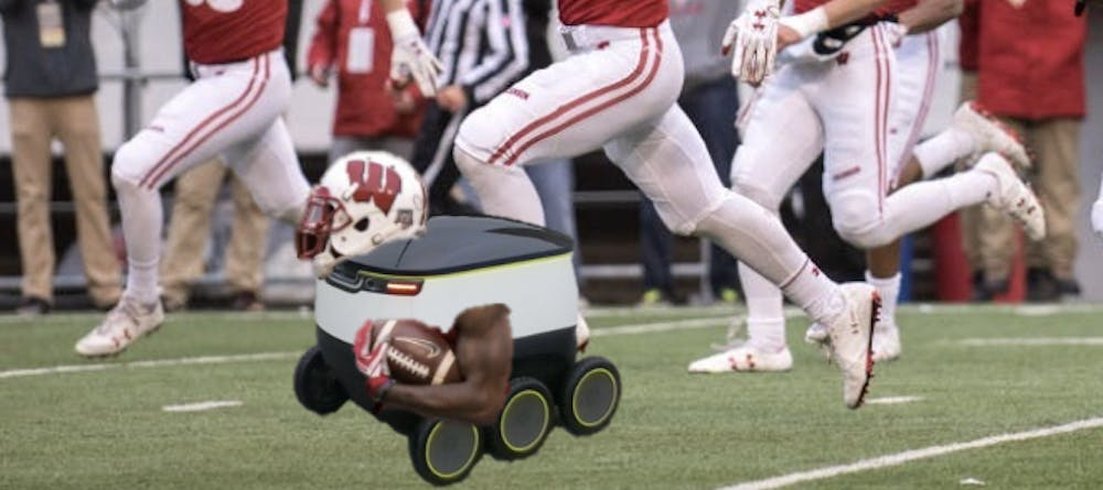 Starship Jonathan Taylor carries the ball down the field during a UW Athletics test of Starship Robots in place of football players.