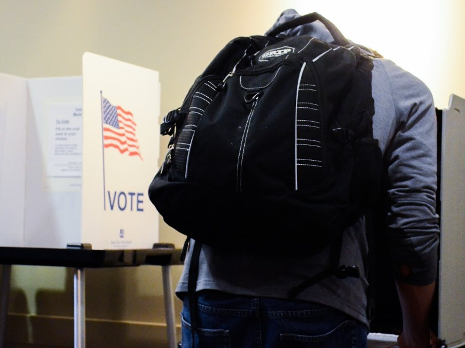 Students, led by UW basketball player Vitto Brown, cast their ballots Monday as early voting began on campus.