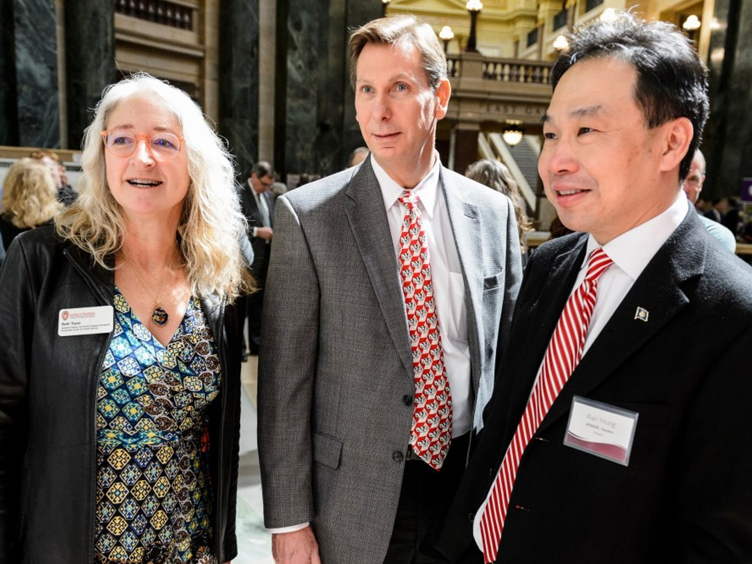 Pictured from left to right, Beth Tryon, assistant director with UW-Madison's Morgridge Center for Public Service; Charlie Hoslet, UW-Madison vice chancellor of university relations; and Alan Yeung, director of US Strategic Initiatives for Foxconn Technology Group, tour student research projects on display during Research in the Rotunda at the Wisconsin State Capitol on April 11, 2018. The outreach event provides students and faculty advisors from across the UW System with the opportunity to share their research findings with Wisconsin legislators, state leaders, UW alumni and members of the public. (Photo by Jeff Miller / UW-Madison)