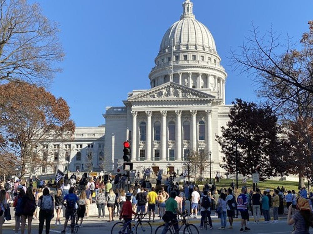 Students, residents and activists alike congregated outside of the State Street corner of the Wisconsin State Capitol Building in what turned out to be a massive gathering.