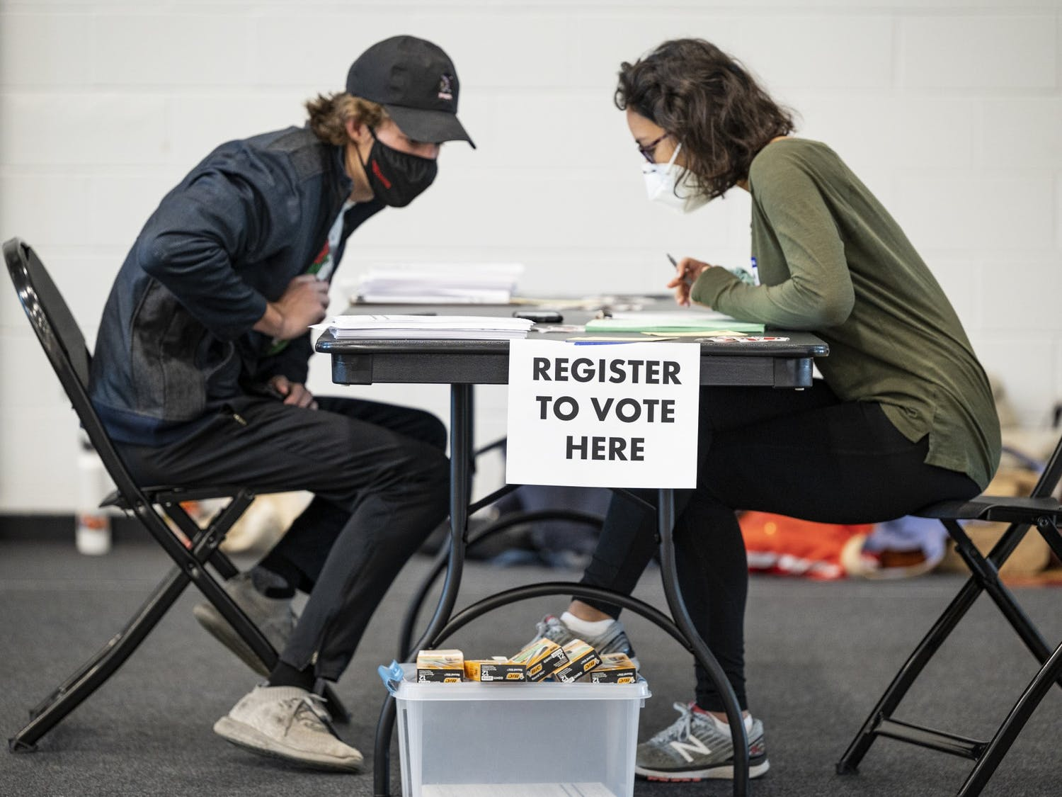 A UW student registers to vote before casting their ballot at the Nicholas Recreation Center polling station.