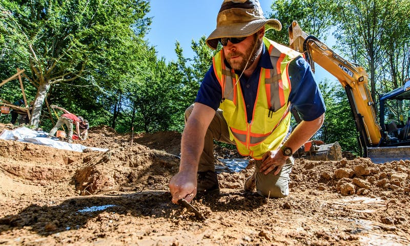 On Aug. 3, 2018, Gregg Jamison, assistant professor of anthropology at the University of Wisconsin-Waukesha, uses a trowel to scrape back soil at a dig site in northern France during a World War II M.I.A. soldier recovery mission that was a joint effort between the University of WisconsinñMadisonís Missing in Action (MIA) Recovery and Identification Project and the U.S. Defense POW/MIA Accounting Agency (DPAA). The work resulted in the identification of Army Air Forces 2nd Lt. Walter B. Stone, 24, of Andalusia, Alabama. He was buried in his hometown on May 11, 2019. (Photo by Bryce Richter /UW-Madison)