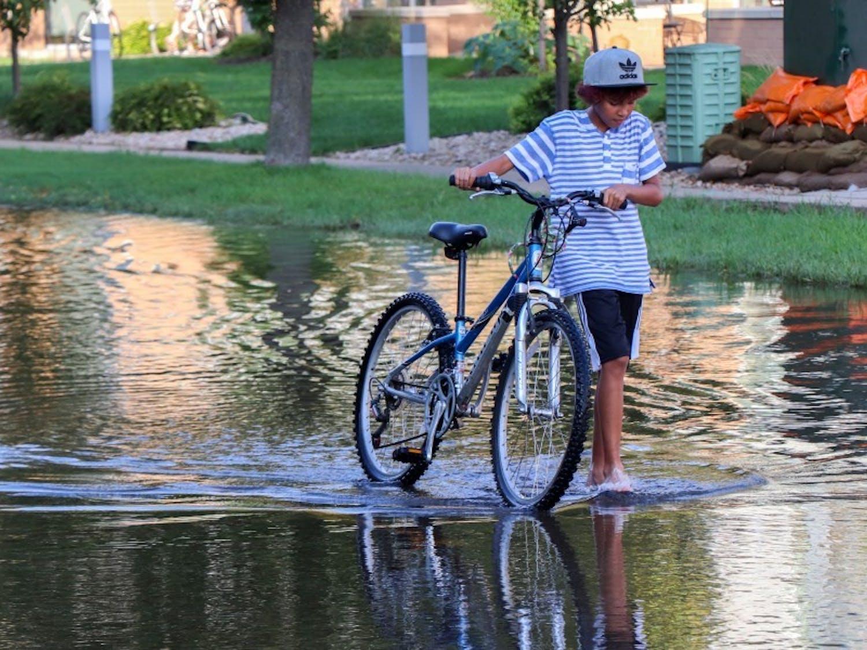 Boy walks his bike through flooding on the Madison Isthmus