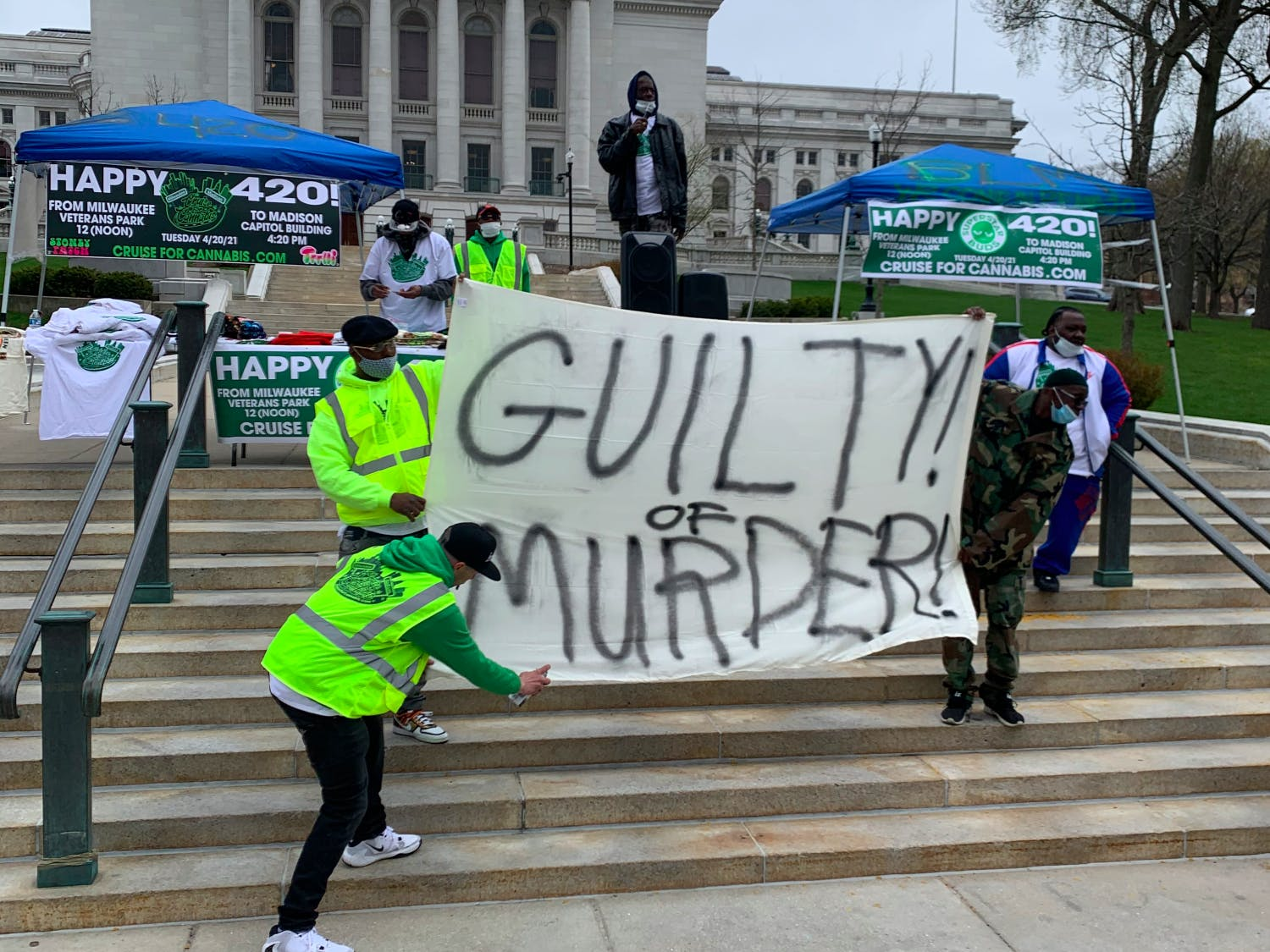 """Photo of a group of men holding up a sign that says """"Guilty of Murder"""" in reference to the Chauvin trial."""
