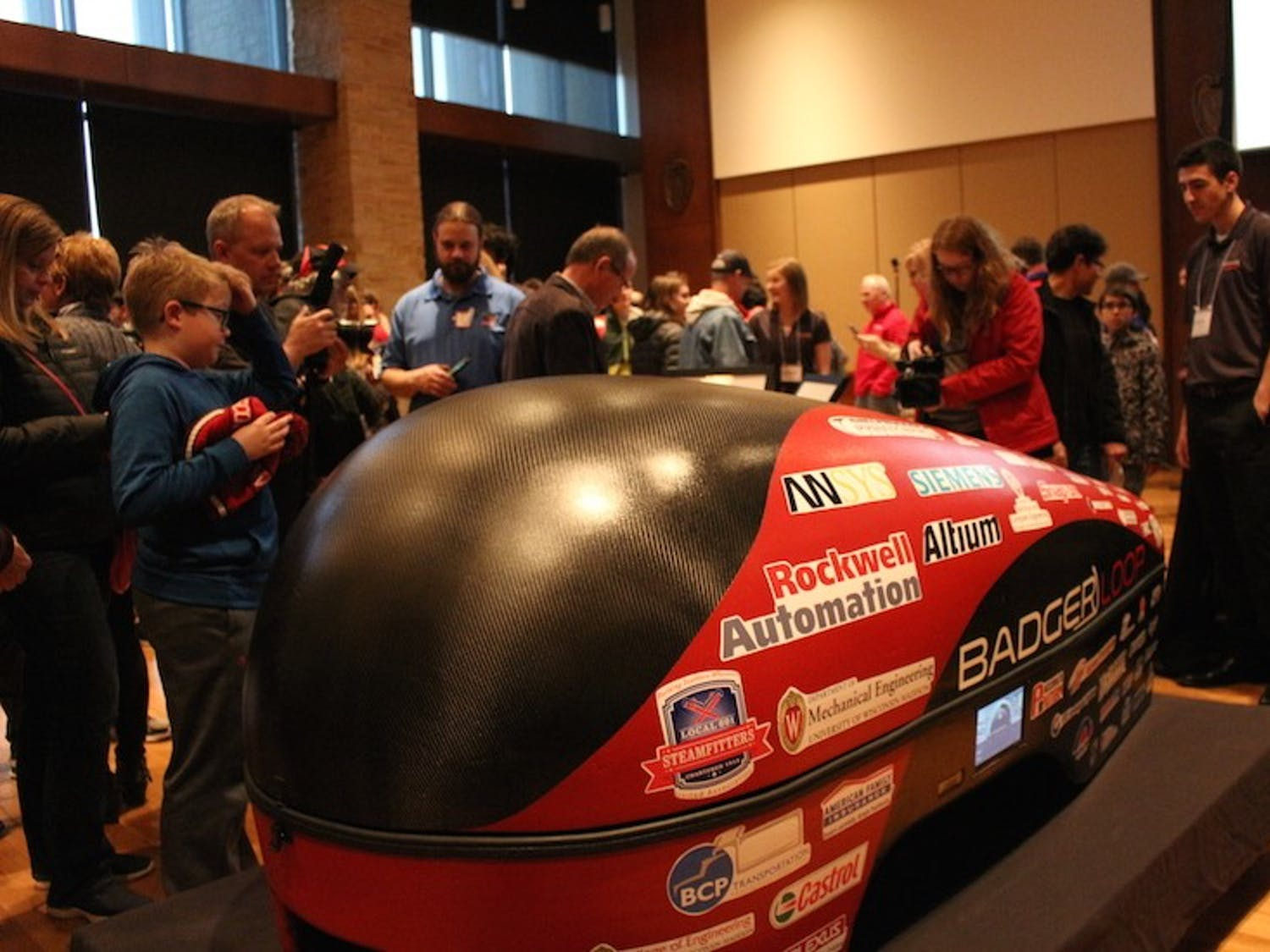 Attendees of all ages view Badgerloop's newest Pod III, an electric-propulsion carbon fiber hyperloop pod.