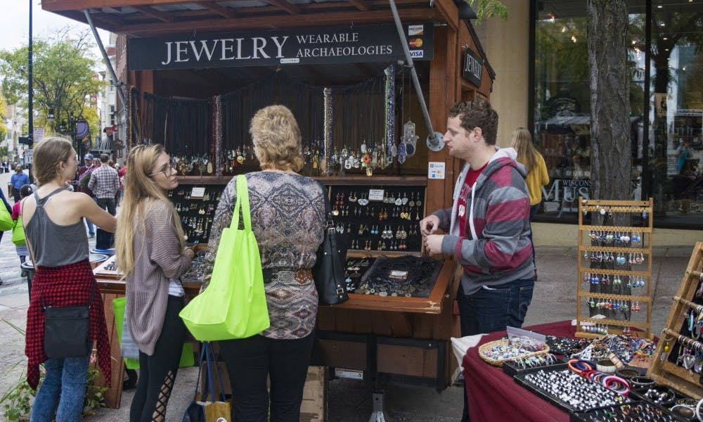 """UW-Madison PhD student Jacob Hellman attempts to sell jewelry to customers at his stand Wearable Archaeologies, a job he said """"doesn't feel like a job"""" because of his love for it."""
