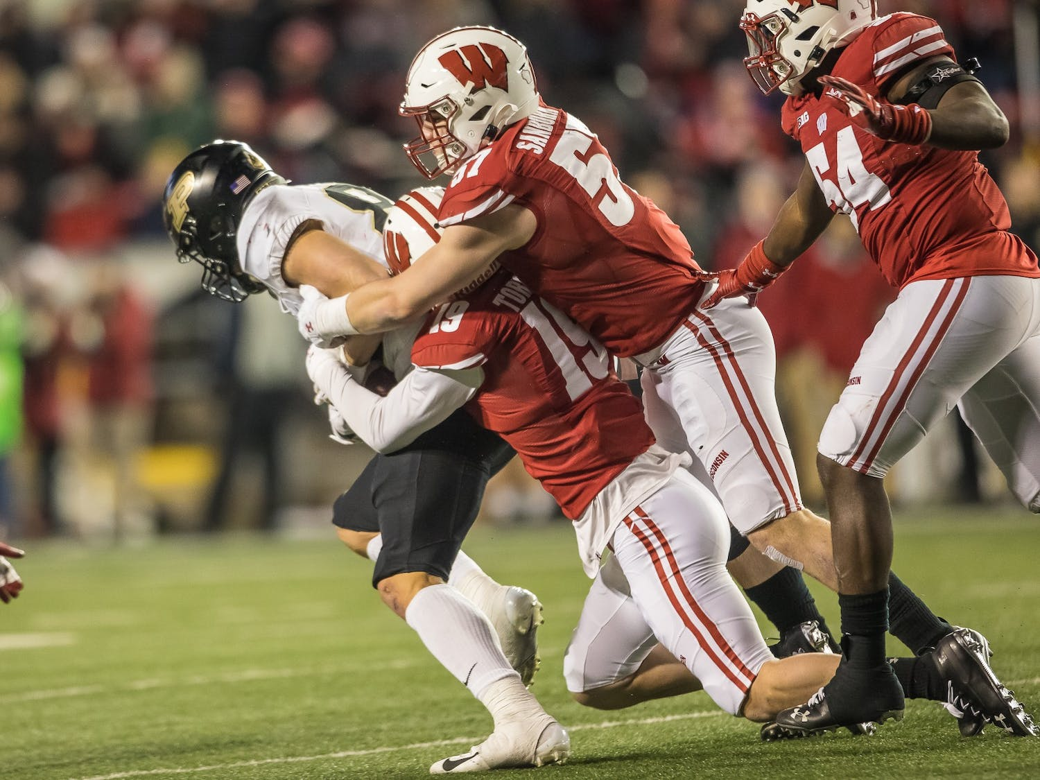 Sanborn makes a tackle with Chris Orr, who graduated and went to the NFL's Carolina Panthers.
