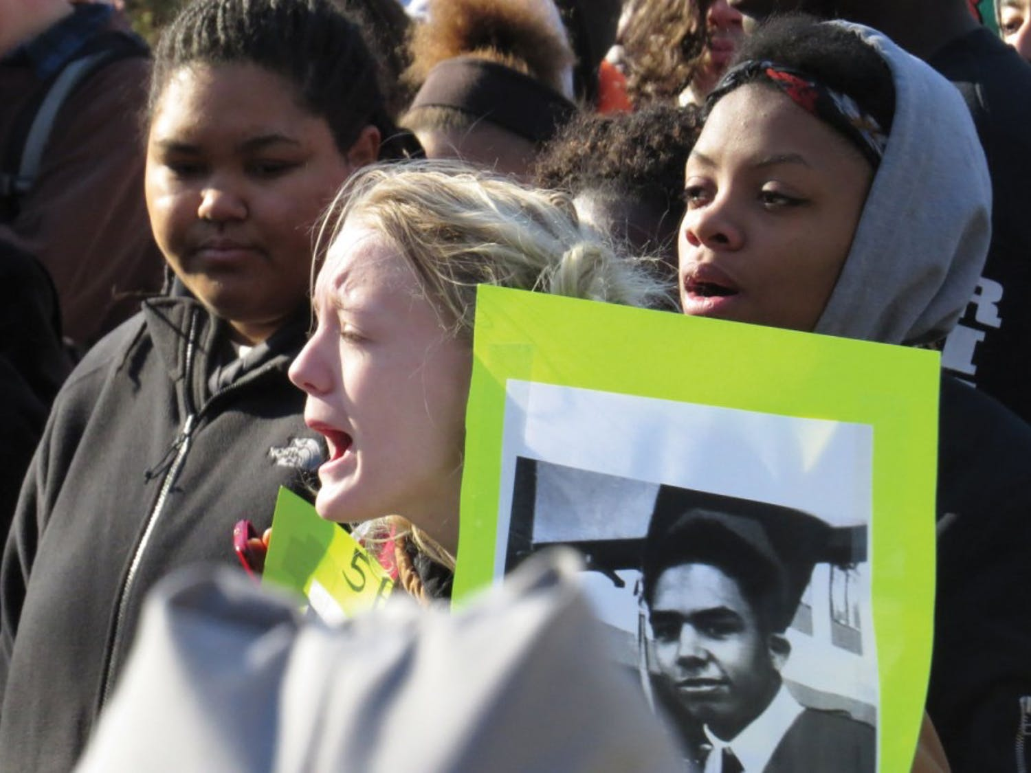 Protesters holding Tony Robinson's picture remind us all of the very human victim of this shooting.