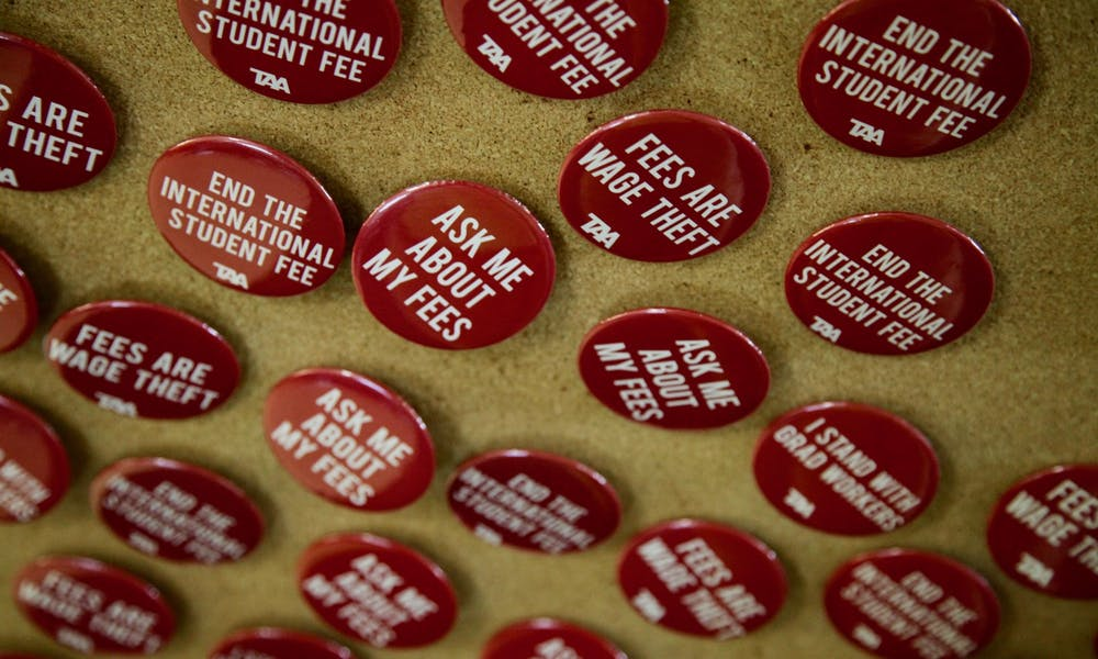 """Photo of buttons which say """"ask me about my fees"""" and """"end the international student fee""""."""